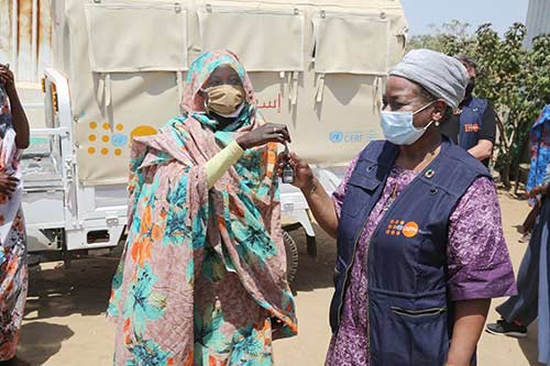 Dr. Kanem hands keys to the ambulance to a local woman community leader. Both women are wearing face masks.
