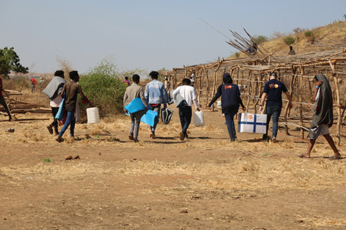 People carry UNFPA-provided supplies through Um Raquba.