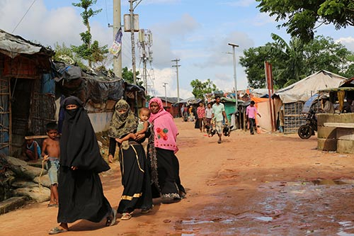 Women walk down a path of a Rohingya refugee camp.