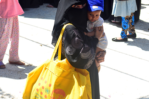 A woman in a niqab holds a baby on one side and carries a yellow dignity kit on the other.