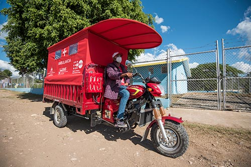 A red motorcycle ambulance stands ready to deliver women to care.
