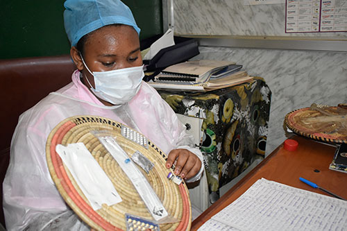 A midwife wearing a mask and hair covering shows clients family planning options available at the clinic, including oral contraceptive pills, injectables and implants.