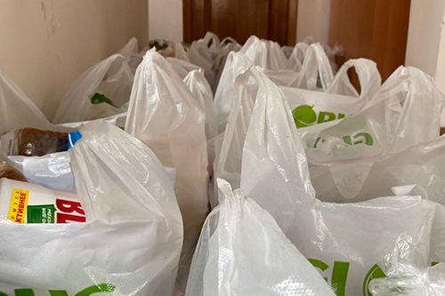 Plastic bags full of food items are accumulated near a door for delivery.