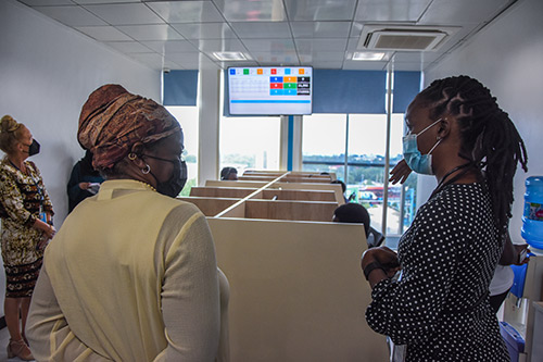 Two women speak in the foreground. Both are wearing face masks. Behind them is a series of cubicles where call centre counsellors are sitting.
