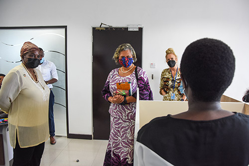Women and men in face masks stand and listen to a counsellor speak about her experiences. The counsellor's back is to the camera.