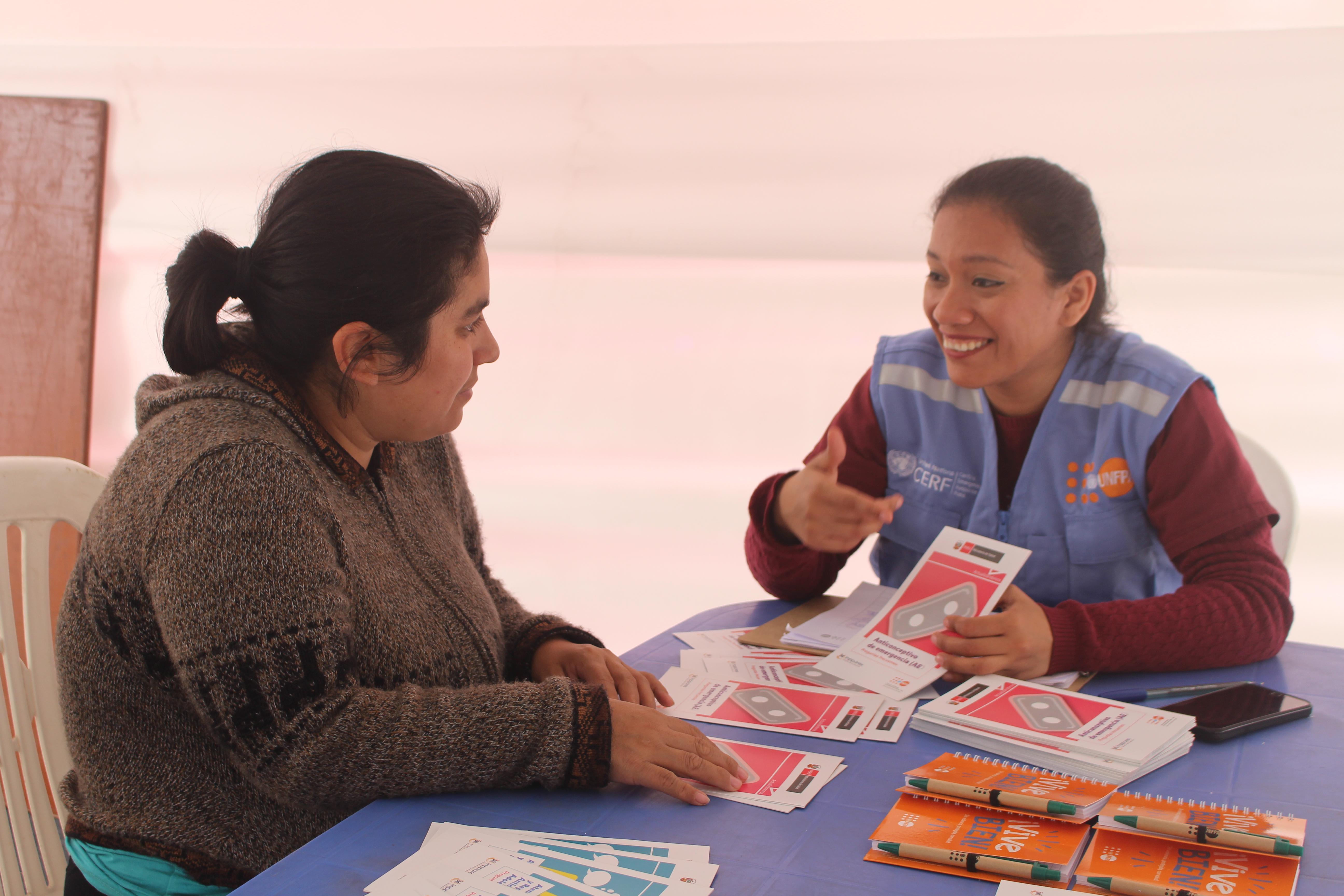Woman speaks with UNFPA staff member