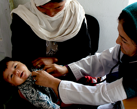 A midwife performs a check-up on a baby.