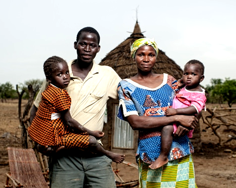 A family with two small children in front of their home.
