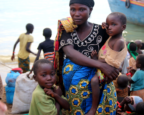 A woman and her two small children flee into Tanzania by boat.