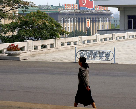 A woman walks past a government building.