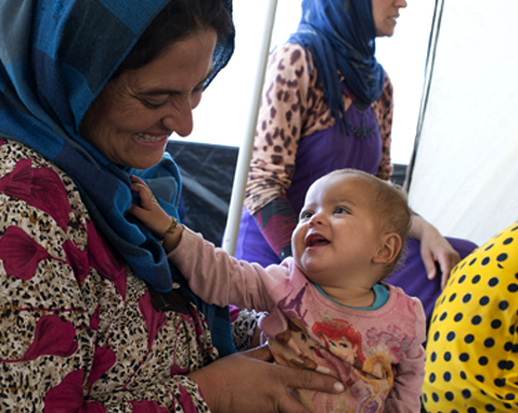 A refugee woman plays with a baby girl in a women's centre.