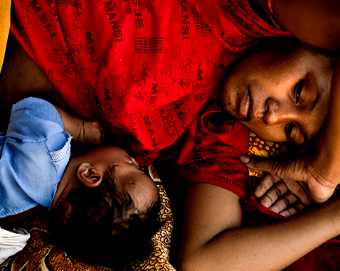 A mother lies next to her newborn baby.