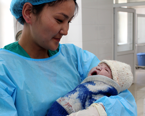 A midwife holds a newborn baby.