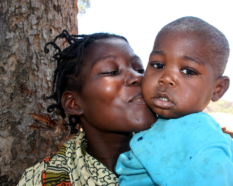 A woman kisses her son on the cheek.