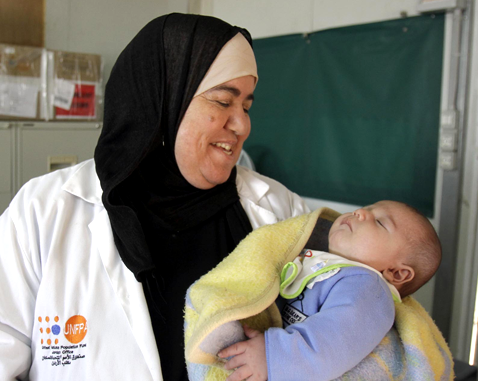 A UNFPA midwife holds a baby.