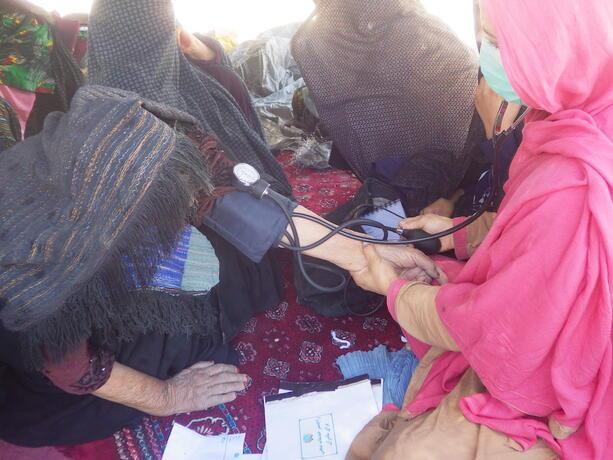 Una partera midiendo la presión arterial de una mujer mayor.