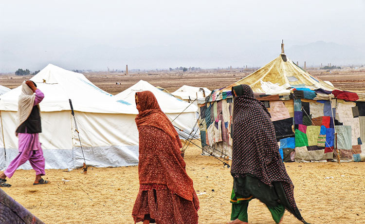Women in full veils covering their faces walk near tents.