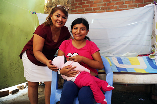 Maritza gave birth at home because her local health centre was shuttered.  She is here with her obstetrician and 9-month-old daughter.