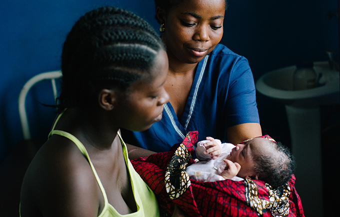 Bendu takes her daughter from a midwife at a health centre in Grand Cape Mount County, Liberia.