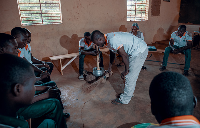 The school for husbands and future husbands teaches men to empower their wives through behavior change. Here, men practice domestic skills to ease the burden on their wives. © UNFPA/Ollivier Girard