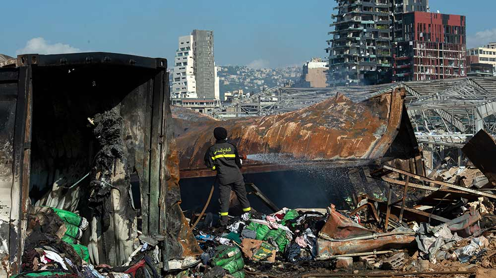 A worker sprays rubble at the site of the blast at the Port of Beirut.