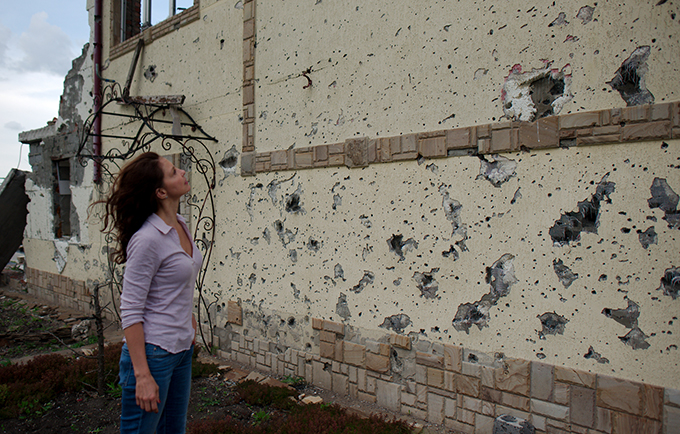 UNFPA Goodwill Ambassador Ashley Judd looks at a shelled building in the Donetsk region of Ukraine. © UNFPA Ukraine/Maks Levin