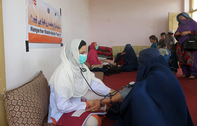 A midwife performs an antenatal check up during a mobile health team visit in Nangarhar Province. © UNFPA Afghanistan