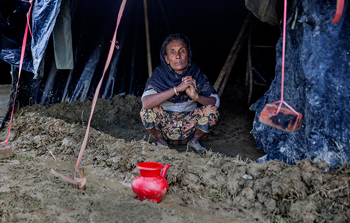 Early monsoon rains have arrived in Cox's Bazar, reigniting fears about the health and safety of refugees. A refugee woman in a muddy camp in late 2017. © UNFPA/Prince Naymuzzaman