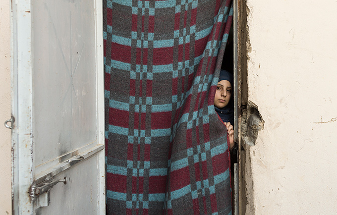 A girl peeks from her one-room shelter in an informal settlment for Syrian refugees in   Al-Marj, Lebanon. Desperation has pushed some Syrian refugee families to see child   marriage as a way to relieve economic pressures. © UNFPA/ David Brunetti