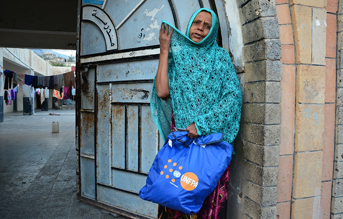 A displaced woman from Taizz receives a dignity kit containing hygiene supplies and other basic items. © UNFPA Yemen