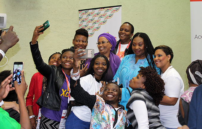 Young people have a right to access to accurate information about their bodies, including how to protect themselves from HIV. Youth pose with singer Yvonne Chaka Chaka at the 21st International AIDS Conference. © UNFPA/Prossy Nakanjako