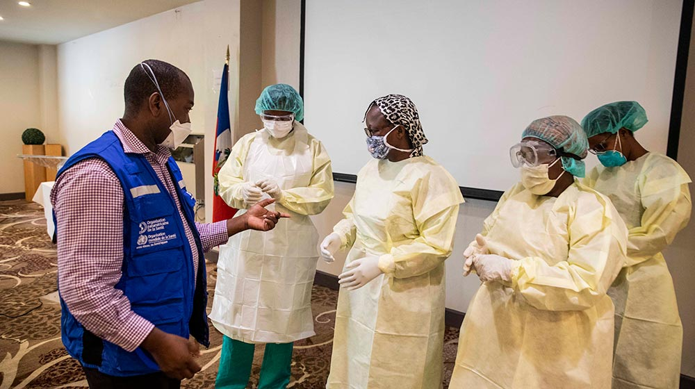 Health workers try on personal protective equipment, including bonnets, face masks, goggles, gowns and gloves, at a demonstration in Haiti.