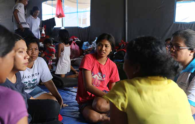 Mothers share their stories with a UNFPA staff at Ulakan Camp. © UNFPA Indonesia/Nun Sol Jang