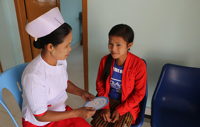 Midwife Nan Win Phyu at the Nam Khoke Rural Health Centre uses a family planning wheel to explain contraceptive options. © UNFPA Myanmar/Si Thu Soe Moe