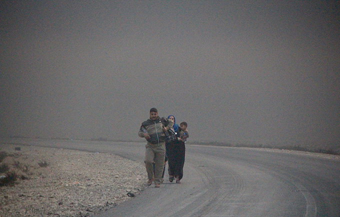 A displaced family walks under a sky blackened by burning oil wells in Qayyarah, south of Mosul. Nineteen oil wells were set ablaze as ISIL retreated from the area. © OCHA/ Themba Linden