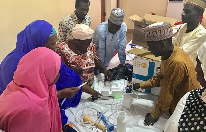 Midwife Hauwa Lassa (third from left) shows colleagues how to use UNFPA-supplied equipment to safely delivery babies. © Anne Wittenberg/UNFPA