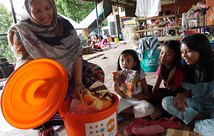 A family opens up a UNFPA-supplied dignity kit at the evacuation centre in the Moneerah Integrated School. © UNFPA