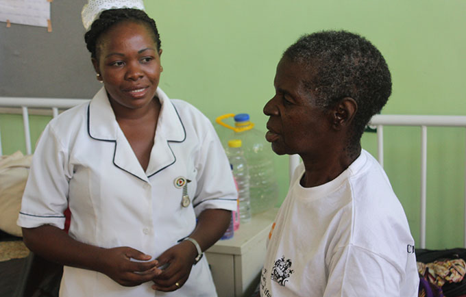 Nurse Lydia Kasiya speaks with obstetric fistula survivor Nachilango Bisolomo at Monkey-bay Community Hospital. © UNFPA Malawi/Henry Chimbali