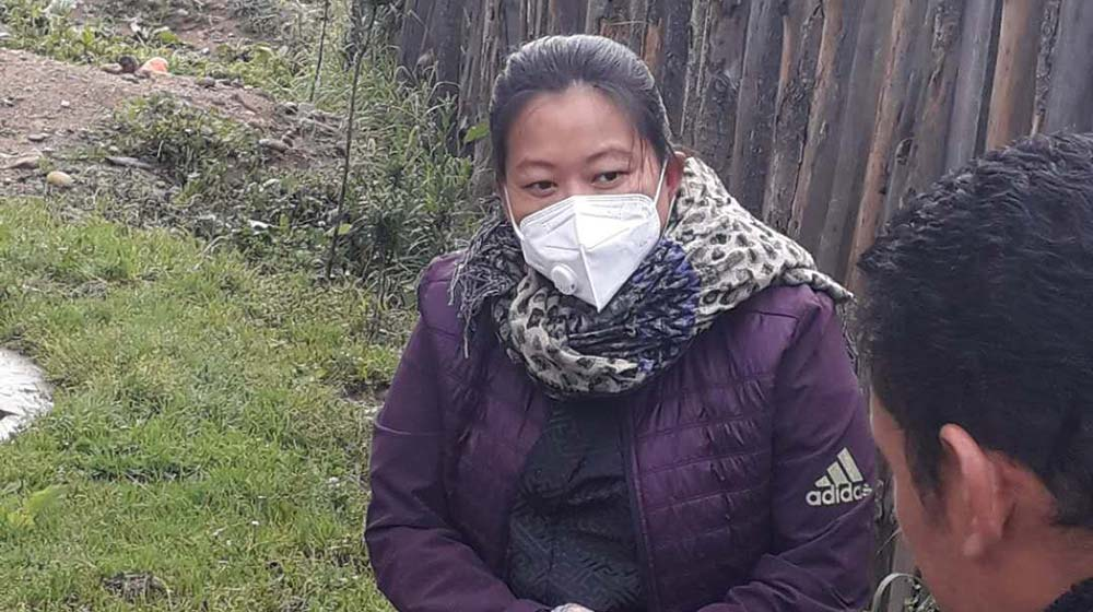 Pema speaks to a client while wearing a face mask and gloves.
