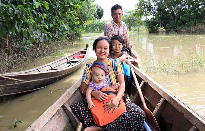 Phoo Ngun, her husband Zaw Moe and their two daughters in the flood-devastated Ayayawady Region. Family planning supplies will help flood-affected women recover without worrying about unplanned pregnancies. © UNFPA Myanmar/Yenny Gamming