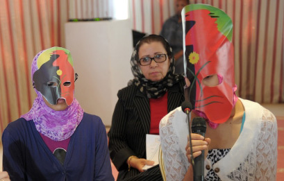 Two adolescent girls are wearing masks and one speaks into a microphone. Behind them stands a moderator.