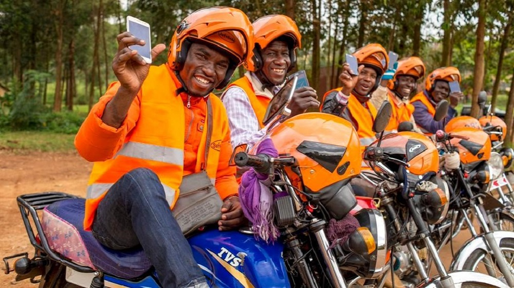 Drivers wearing the orange uniform of the SafeBoda company pose on their motorcycles while holding up mobile phones.