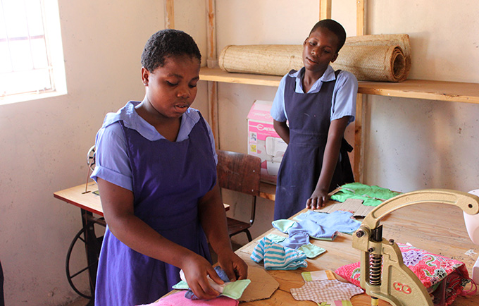 Fatima Muhammed demonstrates how to make a reusable sanitary napkin in her school's sewing room. Classmate Deborah Chavula looks on. © UNFPA Malawi/Henry Chimbali