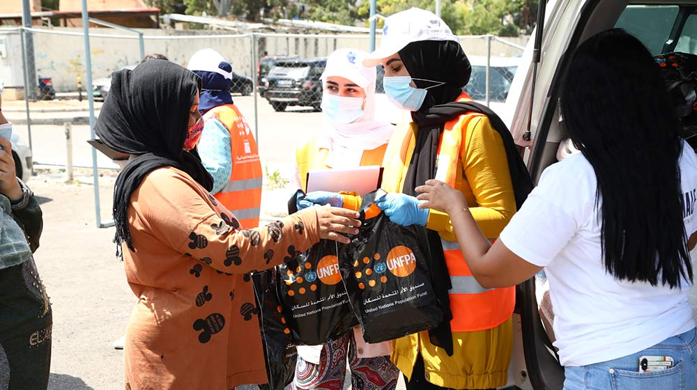 Women in face masks carry UNFPA dignity kits.