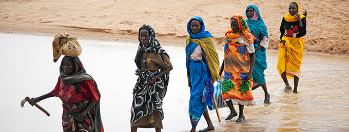 Displaced women are escorted by peacekeepers as they collect firewood in Sudan, in 2010. The women say they fear being assaulted when they leave their homes. Photo credit: UN Photo/Albert González Farran