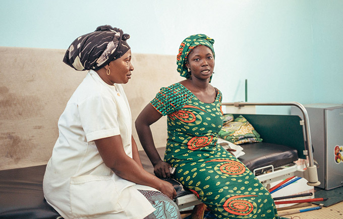 Micheline Yotoudjim (left), a fistula survivor, helps other women with obstetric fistula through the treatment process. Here, she sits with a woman at the National Centre for Fistula Treatment in N'Djamena, Chad. © UNFPA/Ollivier Girard