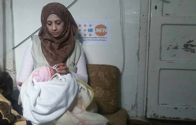 A staff member at the newly opened clinic attends to a newborn baby. Image from UNFPA Syria and Al Mawadda