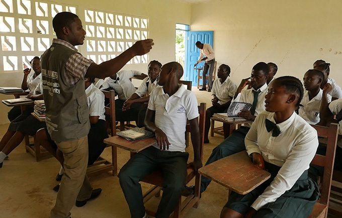 Volunteer James S. Yangbie leads a discussion at the health club he started at Kaytoken Junior High. Talented youth volunteers are meeting reproductive health needs in Liberia, where conflict and the Ebola epidemic had left the health system shattered. © UNFPA/Ruth Fertig