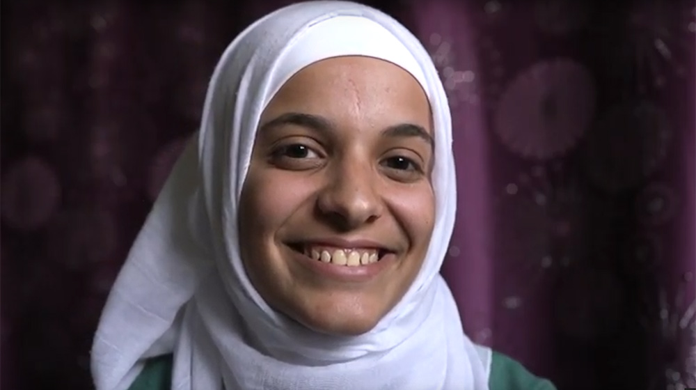 Yanal, a Syrian refugee in Jordan, smiles broadly.