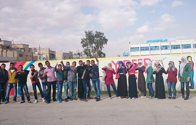 Palestinian youth and Y-Peer trainers from Syria and Jordan stand in front of a mural they have created at a school run by the UN Relief and Works Agency in Zarqa, Jordan. © Y-Peer/Abdelbari Hamad